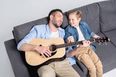 father with son playing on guitar 4