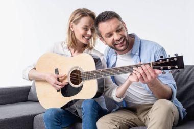 man teaching woman playing guitar