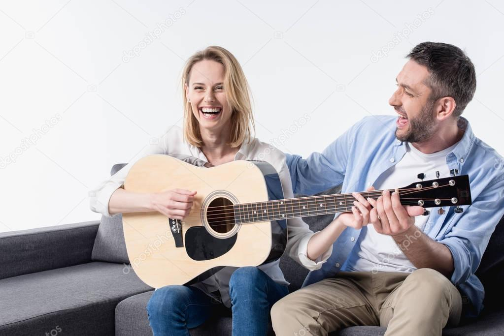 man teaching woman playing guitar