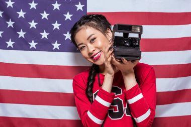 woman holding retro photo camera
