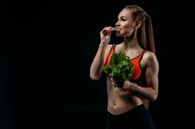 sportswoman eating salad leaves