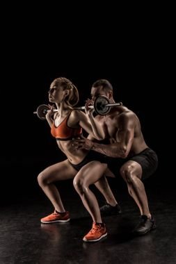 Couple exercising with barbell