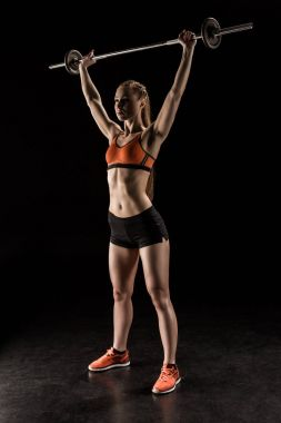 Sportswoman training with barbell