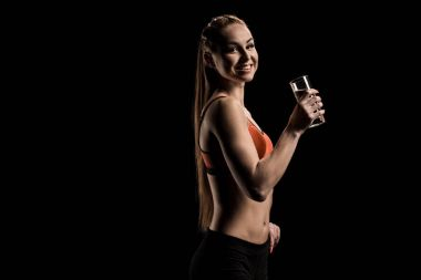 smiling sportswoman holding glass of water