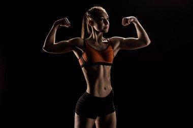young caucasian sportswoman flexing biceps