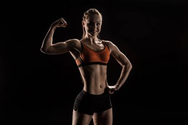 young smiling sportswoman flexing biceps