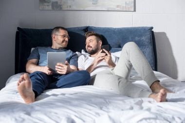 Homosexual couple using digital devices