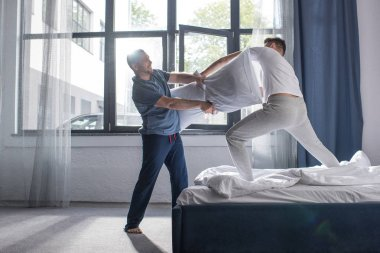 Homosexual couple fighting with pillows