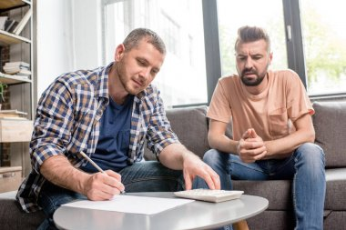Homosexual couple counting budget