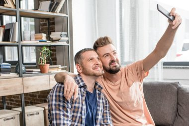 homosexual couple taking selfie on smartphone