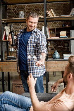 man giving glass of wine to boyfriend