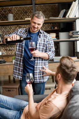 man pouring wine during talk with boyfriend