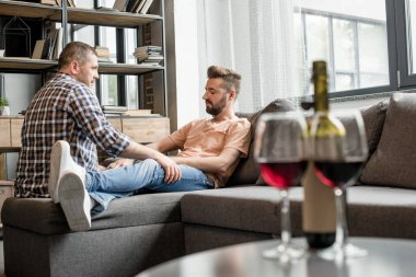 homosexual couple talking while sitting on sofa