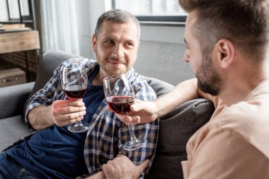 homosexual couple drinking wine at home