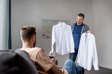 homosexual couple choosing shirts at home