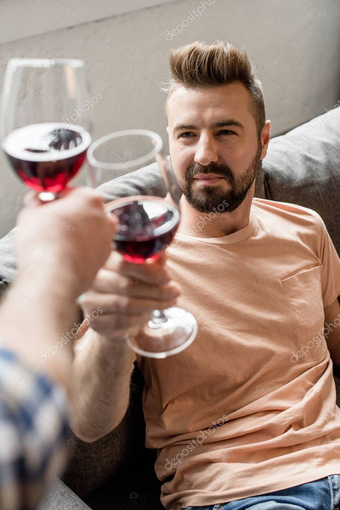 homosexual couple clinking with wine at home
