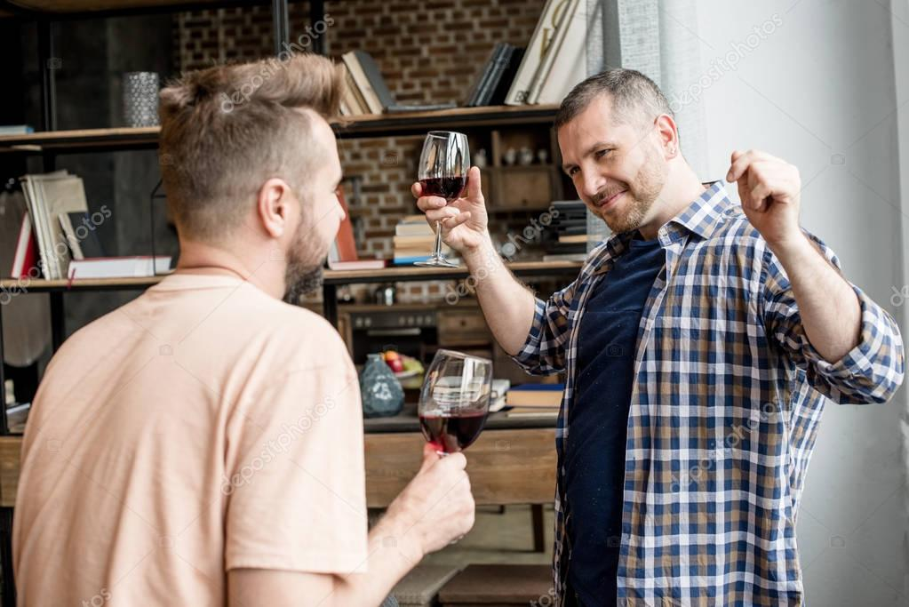 homosexual couple talking and drinking wine