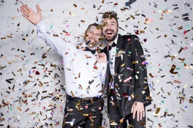 happy homosexual couple celebrating with confetti