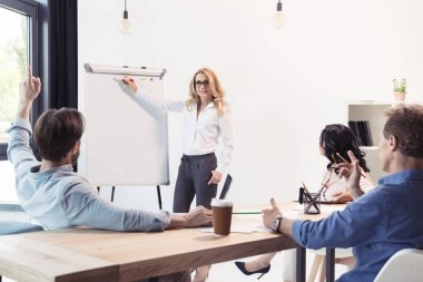 Blonde businesswoman in eyeglasses pointing at blank whiteboard and looking at colleagues stock vector