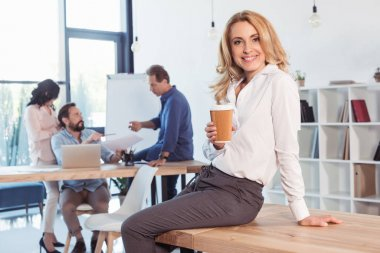 Smiling blonde businesswoman sitting on table and drinking coffee while colleagues working behind stock vector