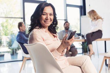 mature asian businesswoman using smartphone