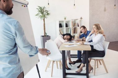 businessman writing on whiteboard while colleagues sitting