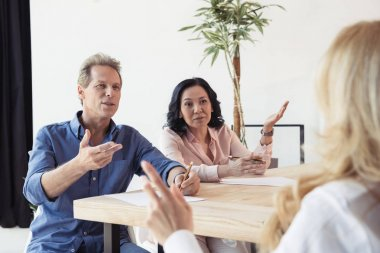 middle aged colleagues disputing at meeting