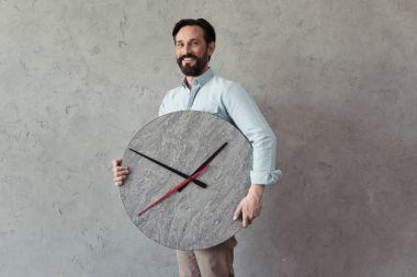smiling mature man holding clock