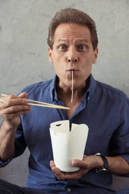 mature man fooling around with noodles