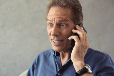 man talking on smartphone with facial expression