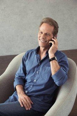 smiling mature man talking on smartphone
