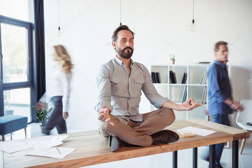 Businessman meditating in office