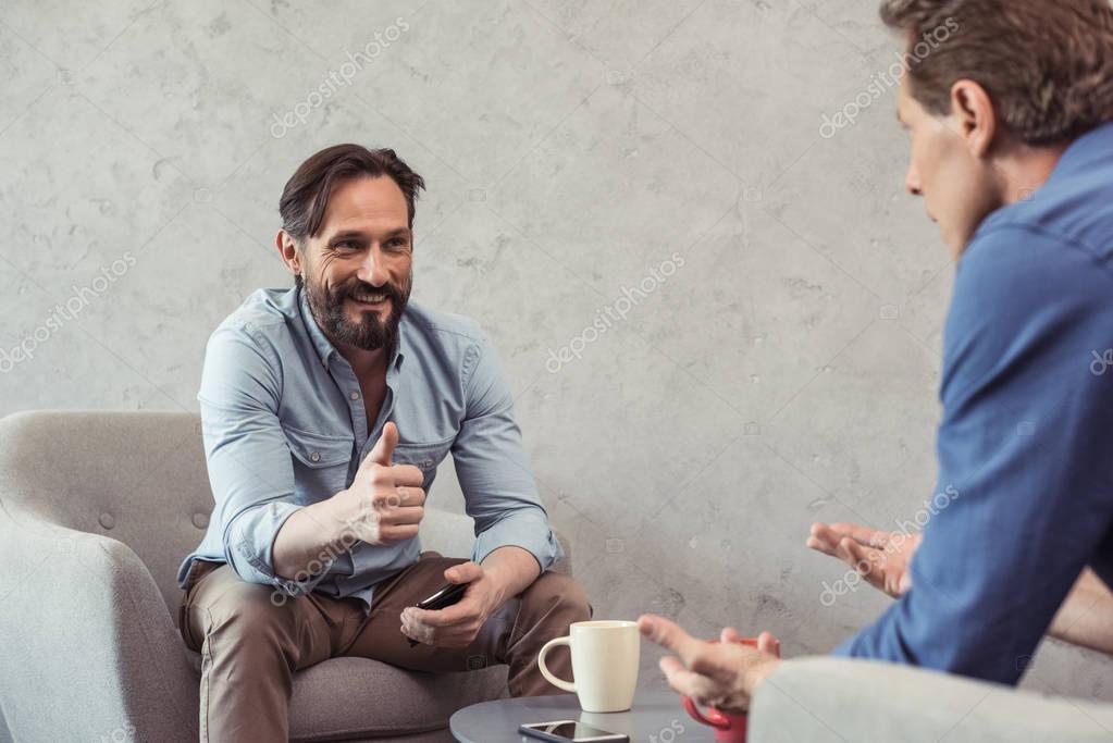 middle aged businessmen talking at break