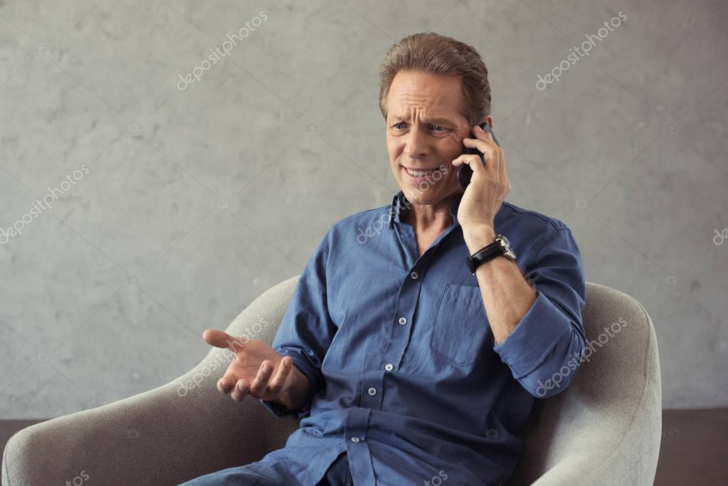 emotional mature man talking on smartphone