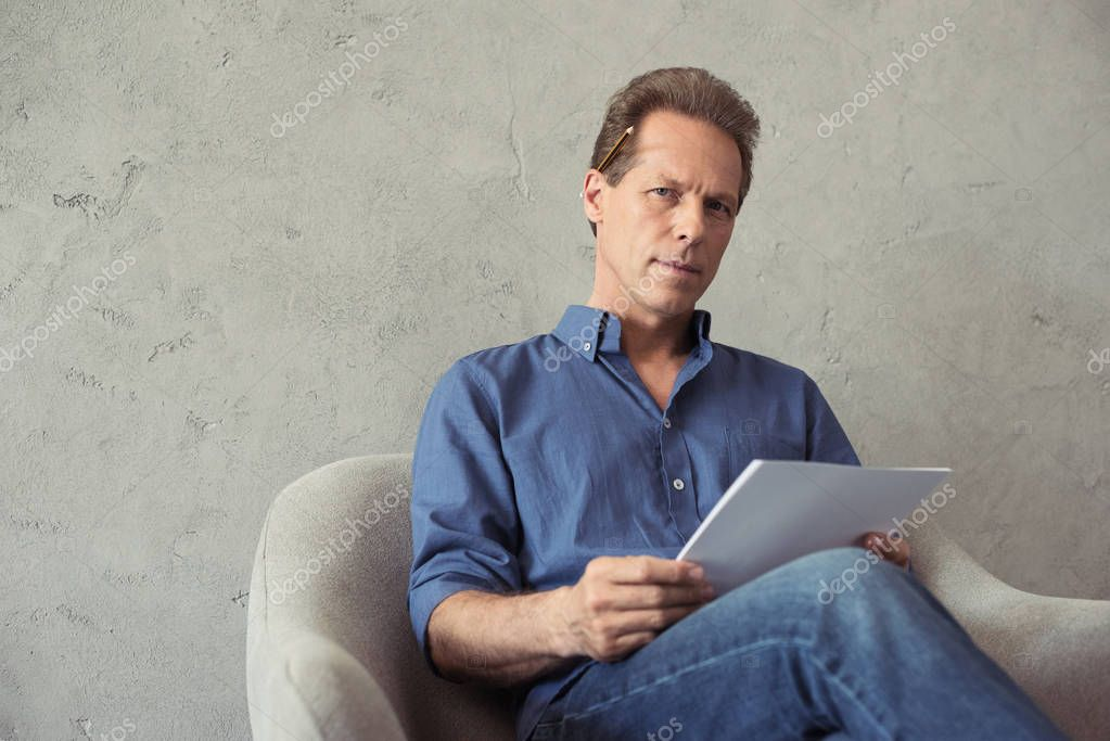 artist with pencil and paper sitting on armchair