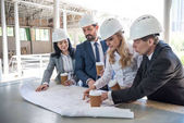 contractors in formal wear working with blueprints
