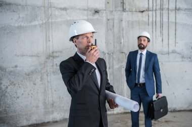 Professional architect holding blueprint and using walkie-talkie while colleague with briefcase standing behind stock vector