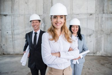 Professional team of architects in helmets standing together and smiling at camera stock vector