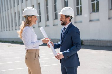 Professional middle aged architects in helmets holding blueprint and discussing project stock vector