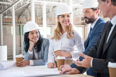 Team of multiethnic architects in suits working with blueprints at construction area stock vector