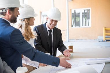 Mature contractors in formal wear working with blueprints at construction stock vector