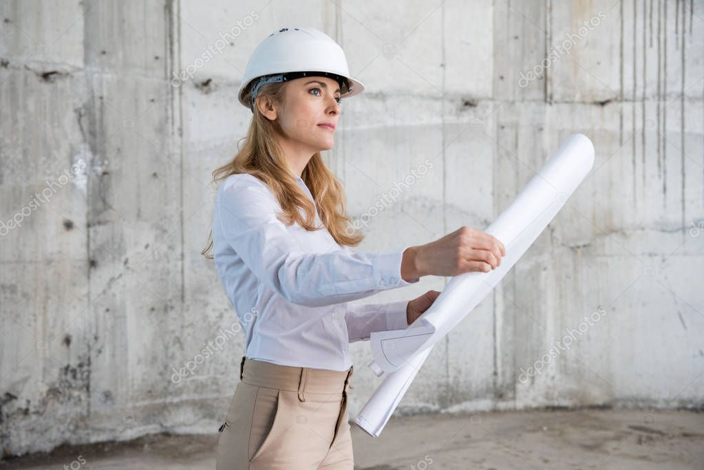 Beautiful blonde architect in helmet working with blueprint and looking away at construction site stock vector