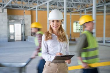 mature contractor making notes at clipboard