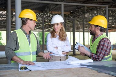 Mature builders and contractor talking during work on construction site stock vector