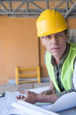 Mature architect looking at camera while working with blueprints at construction site stock vector
