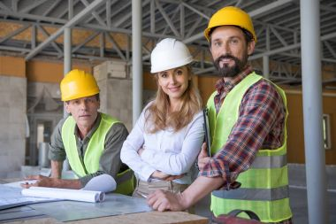 Middle aged constructors and contractor looking at camera during work on construction site stock vector
