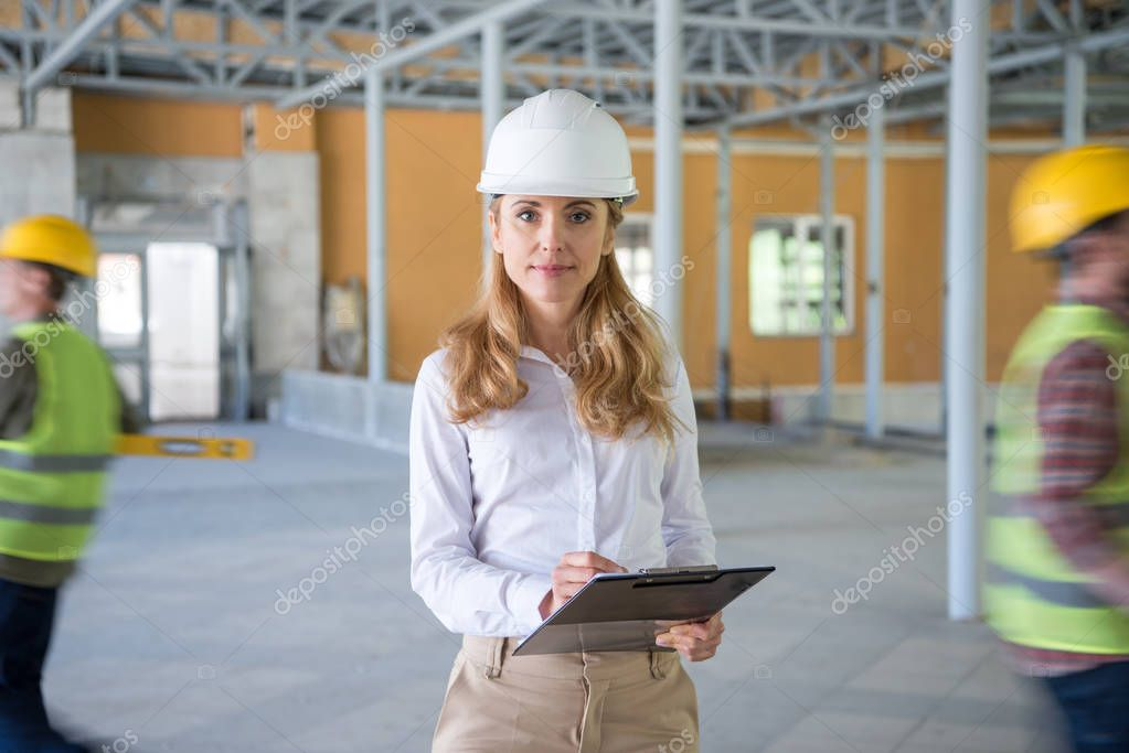 Mature contractor in helmet making notes at clipboard and looking at camera stock vector