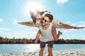 couple piggybacking on beach