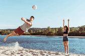 Přáteli, kteří hrají volejbal na pláži