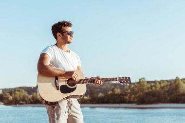 young man playing guitar on riverside